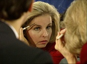 Woman looks in the mirror and grooms her eyebrows with eyebrow brush, Washington D.C