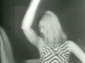 Blonde girl dressed in monochrome dress dances in club and claps hands, USA; 1965