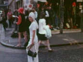 Woman dressed in white with long platinum blond hair walks along Carnaby Street, turns to look at camera, London; 1960\%27s