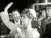 Italian actress Gina Lollobrigida waves to crowd as she arrives at film premiere, Vienna; 1966