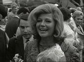 Crowds of press are held back as Hollywood actress Rita Hayworth steps off aircraft at Vienna airport; May 66