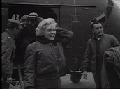 Marilyn Monroe steps down from US military helicopter before getting into car and posing with officer during tour of military bases, Korea; Feb 54