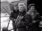 Marilyn Monroe arrives at US military base before being escorted by Military Police, Korea; Feb 54