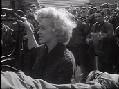 US military personnel stand either side of sign welcoming Hollywood star Marilyn Monroe, Monroe climbs into jeep and waves to troops before departing in convoy during entertainment tour, Korea; Feb 54