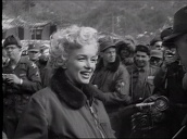 Marilyn Monroe smiles and poses as US troops with cameras take photographs, Korea; Feb 54