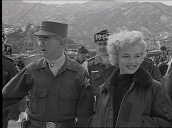 Marilyn Monroe smiles and poses with army official and Military Police during entertainment tour for US troops, Korea; Feb 54