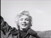 Marilyn Monroe standing inside US army jeep surrounded by Military Police waves and blows kiss to troops, Korea; Feb 54