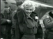 Marilyn Monroe walks with US troops through army base before stepping into awaiting car during entertainment tour, Korea; Feb 54