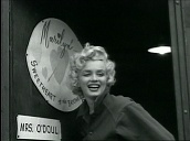 "Marilyn Monroe waves to US troops in front of door sign saying, ""Marilyn - Sweetheart of the Bayonet Division"", during entertainment tour, Korea; Feb 54"
