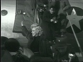 Marilyn Monroe waves as she disembarks US air force plane before being surrounded by troops, Korea; Feb 54