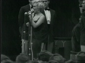 Marilyn Monroe performs on stage with backing singers for US troops, Korea; Feb 54