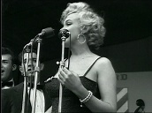 Marilyn Monroe sings seductively on stage to crowd of US troops, Korea; Feb 54