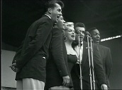 Marilyn Monroe with backing singers entertains US troops before leaving stage, Korea; Feb 54