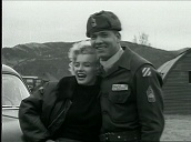 Marilyn Monroe waves and blows kiss as she arrives in jeep at US army base before posing with troops during entertainment tour, Korea; Feb 54