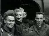 Marilyn Monroe poses with troops before departing in US army helicopter, Korea; Feb 54